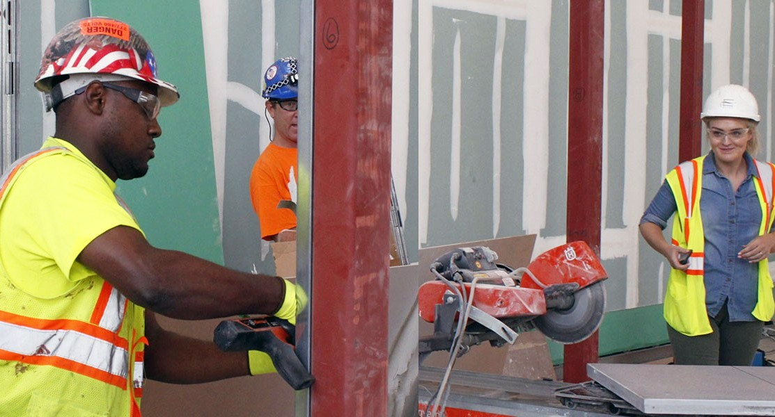 Construction workers of different genders and racial backgrounds working together.